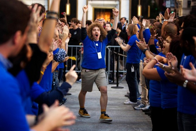 Apple employees celebrate the release of the Apple iPhone 5 phone outside of the Apple Store on 5th Avenue in New York, September 21, 2012. Apple fans queued around city blocks worldwide on Friday to get their hands on the new iPhone 5 - but grumbles about inaccurate maps tempered the excitement. REUTERS/Lucas Jackson (UNITED STATES - Tags: BUSINESS TELECOMS)