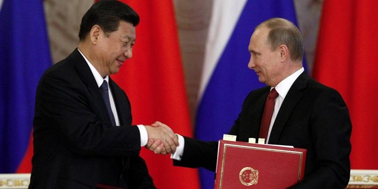 Čínsky prezident Xi Jinping si podáva ruku s ruským prezidentom Vladimírom Putinom.