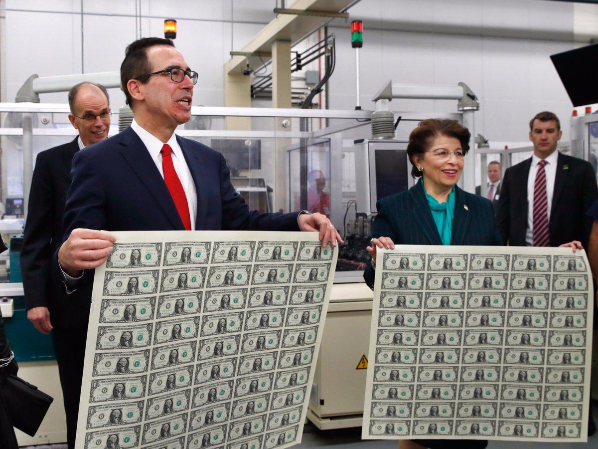 Tajomník ministerstva financií Steven Mnuchin a americká pokladníčka Jovita Carranzaová držia listy nových 1 dolárových bankoviek. Ide o prvé bankovky s podpismi Mnuchina a Carranzyovej. (fotografia zo stredy 15. novembra 2017). Zdroj: Jacquelyn Martin/AP