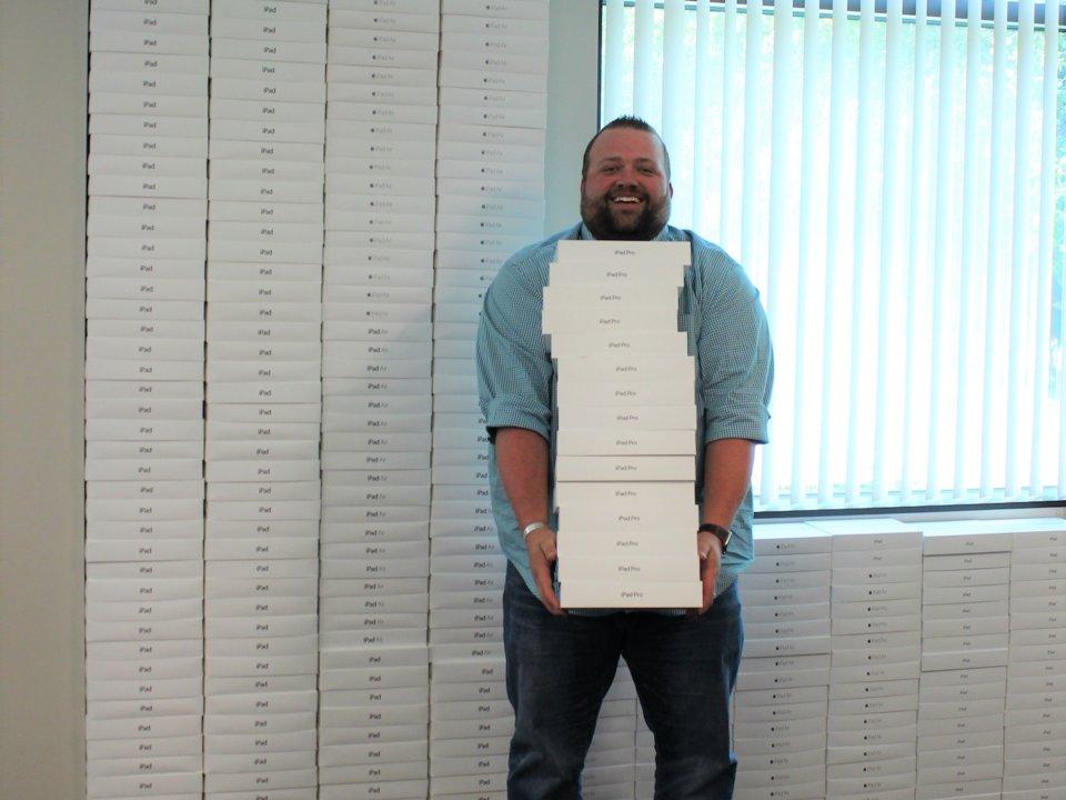 Todd Wynne ukazuje stenu prázdnych krabíc zo stoviek iPadov, ktoré spoločnosť kúpila.