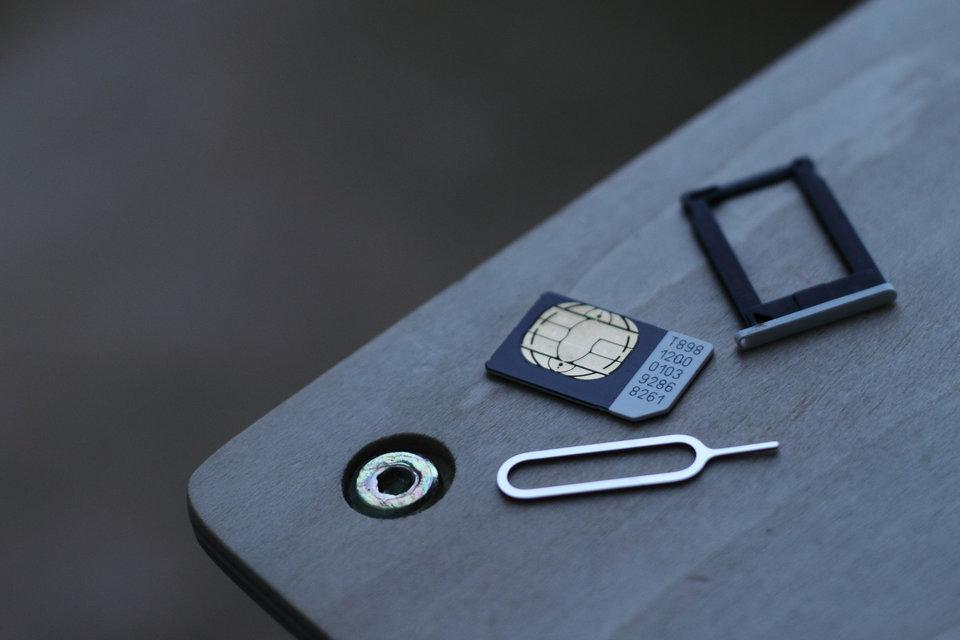 SIM karta, zásobník SIM karty a nástroj na odstránenie zásobníka z telefónu.