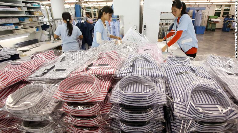 Pracovníci balia košele v továrni vo vietnamskom Hanoji v roku 2014. Obchodné napätie urýchlilo presun výroby z Číny do krajín v juhovýchodnej Ázie, kde je pracovná sila lacnejšou.