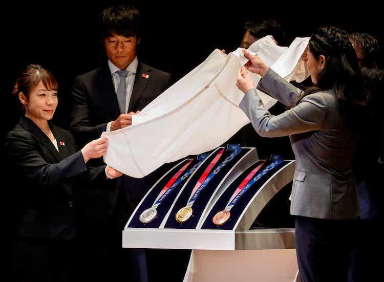 Olympijskí medailisti odhalili olympijské medaily v Tokiu (strieborné, zlaté a bronzové) počas slávnosti vrámci Tokijského fóra.
