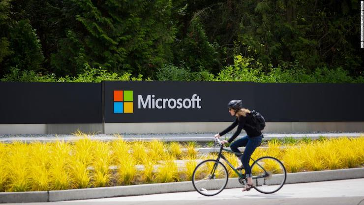 A woman rides a bicycle past a Microsoft Corp. sign on the company's main campus in Redmond, Washington, U.S., on Wednesday, July 17, 2014. Microsoft Corp. said it will eliminate as many as 18,000 jobs, the largest round of cuts in its history, as Chief Executive Officer Satya Nadella integrates Nokia Oyj's handset unit and slims down the software maker. Photographer: Mike Kane/Bloomberg via Getty Images