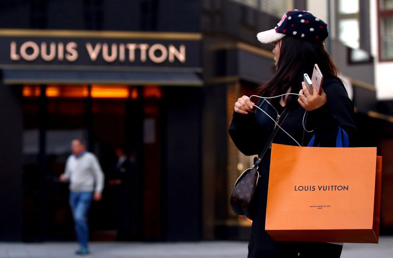 FILE PHOTO: A woman with a Louis Vuitton-branded shopping bag looks towards the entrance of a branch store by LVMH Moet Hennessy Louis Vuitton in Vienna, Austria October 4, 2018. REUTERS/Lisi Niesner