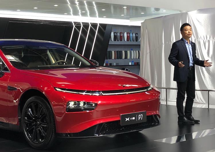 Generálny riaditeľ spoločnosti Xpeng He Xiaopeng stojí vedľa elektrického sedanu P7 spoločnosti.