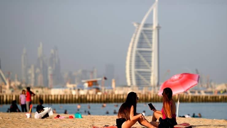 Opaľujúce sa ženy pozdĺž pláže v Dubajskom zálive, zatiaľ čo v pozadí je hotel Burj al-Arab.