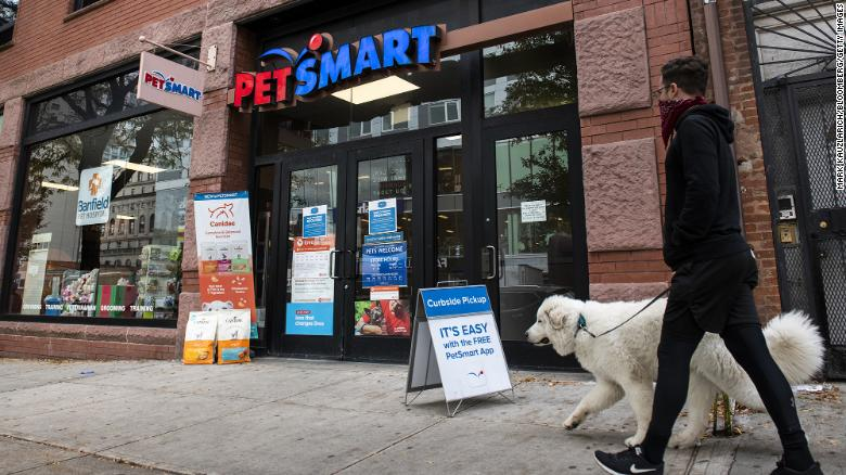 A pedestrian wearing a protective mask walks a dog outside a PetSmart store in the Brooklyn borough of New York, U.S., on Tuesday, Oct. 27, 2020. PetSmart Inc.??is kicking off a??$2.35 billion??junk bond offering as part of a larger financing package that will separate the company from its online counterpart??Chewy Inc. Photographer: Mark Kauzlarich/Bloomberg via Getty Images