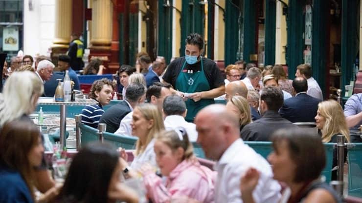 Čašník s rúškom na tvári obsluhujúci zákazníkom v reštaurácii.
